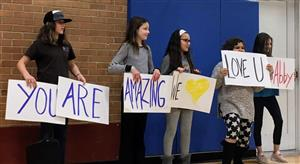 Students hold signs in support of Abby George