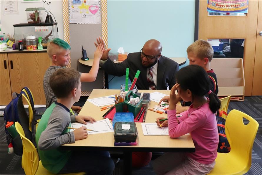Superintendent Lewis high-fives a student while visiting a school