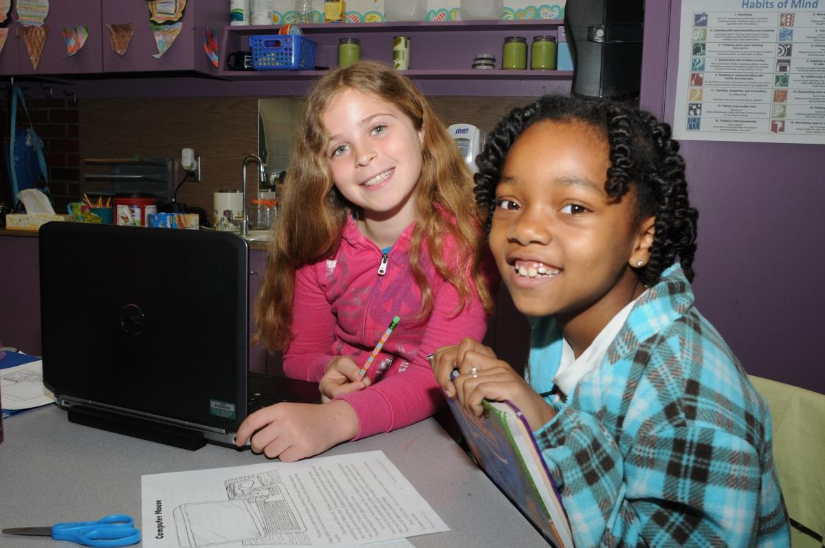 Two elementary students work on laptops in their classroom